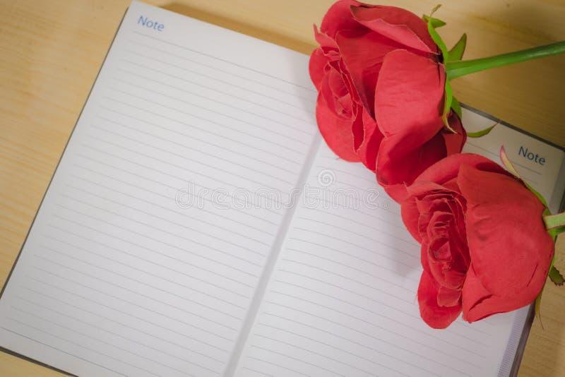 Rose roja en el cuaderno imágenes de archivo libres de regalías