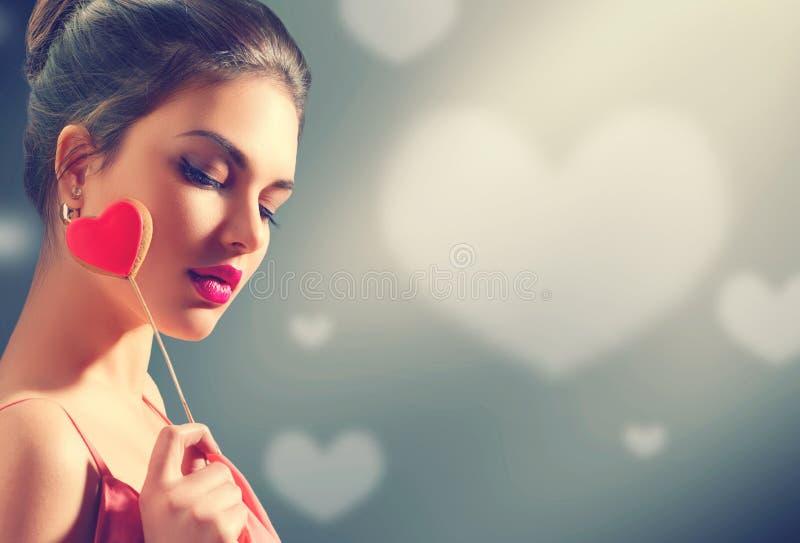 Rose roja Muchacha modelo joven de la belleza con la galleta en forma de corazón de la tarjeta del día de San Valentín imagenes de archivo