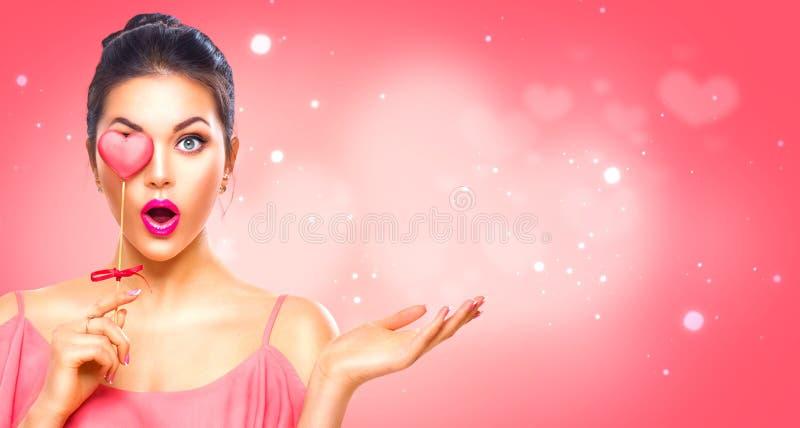 Rose roja Muchacha modelo joven de la belleza con la galleta en forma de corazón de la tarjeta del día de San Valentín foto de archivo
