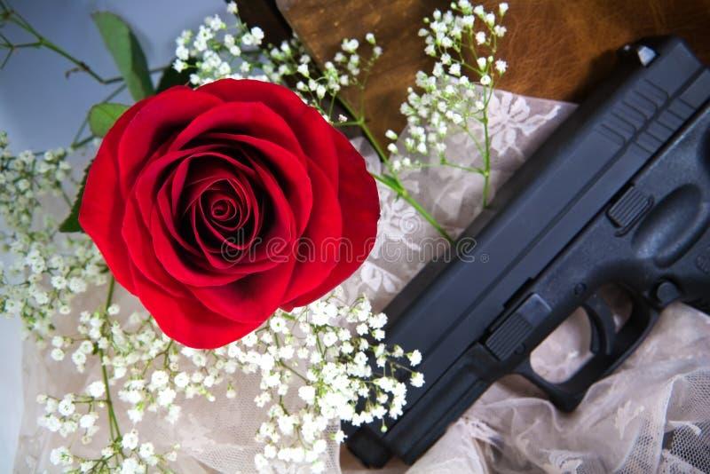 Rose roja y respiración de Babys con un arma foto de archivo