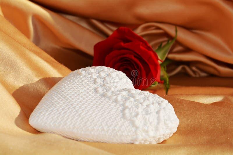 Rose romantique de coeur et de rouge sur le fond d'or photo stock