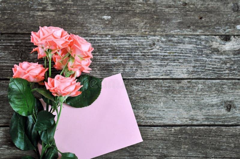Rose rosa e carta intestata della tonalità di corallo delicata su fondo di legno rustico Priorità bassa del biglietto di S Carta  fotografia stock