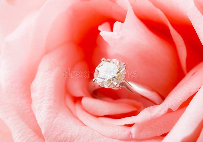 Rose rosada y anillo de diamante acurrucado dentro imagen de archivo libre de regalías