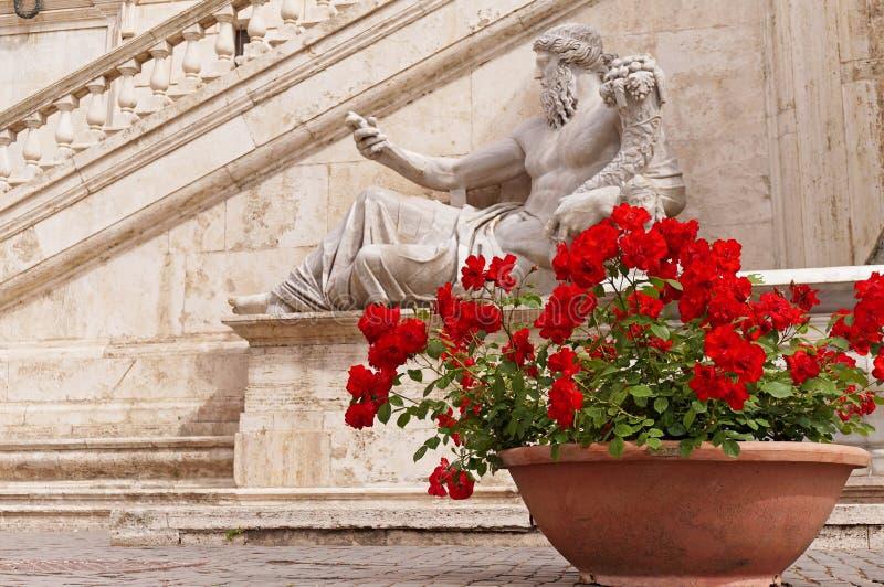 Rose rosse accanto alla statua di Nile God a Roma immagine stock libera da diritti