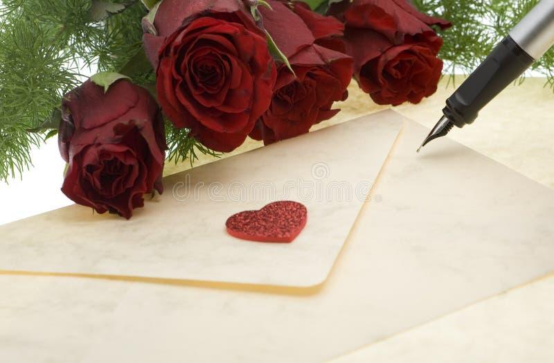 Rose rosse con la busta e la penna immagini stock