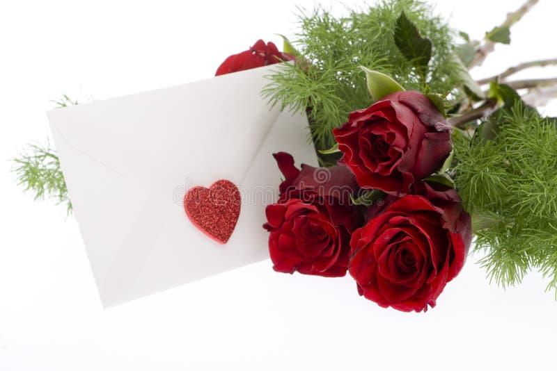 Rose rosse con la busta ed il cuore fotografia stock
