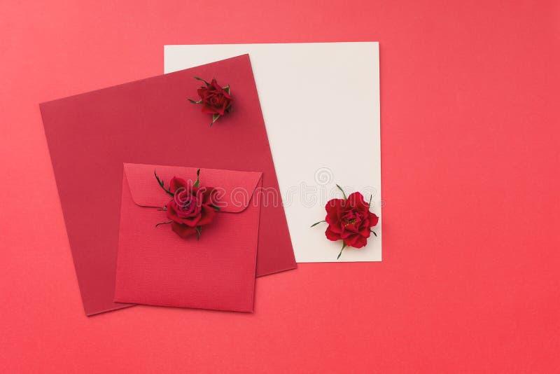 Rose rosse con una cartolina d'auguri e le buste in bianco immagine stock libera da diritti