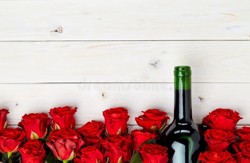 Rose rosse e vino su fondo bianco fotografia stock