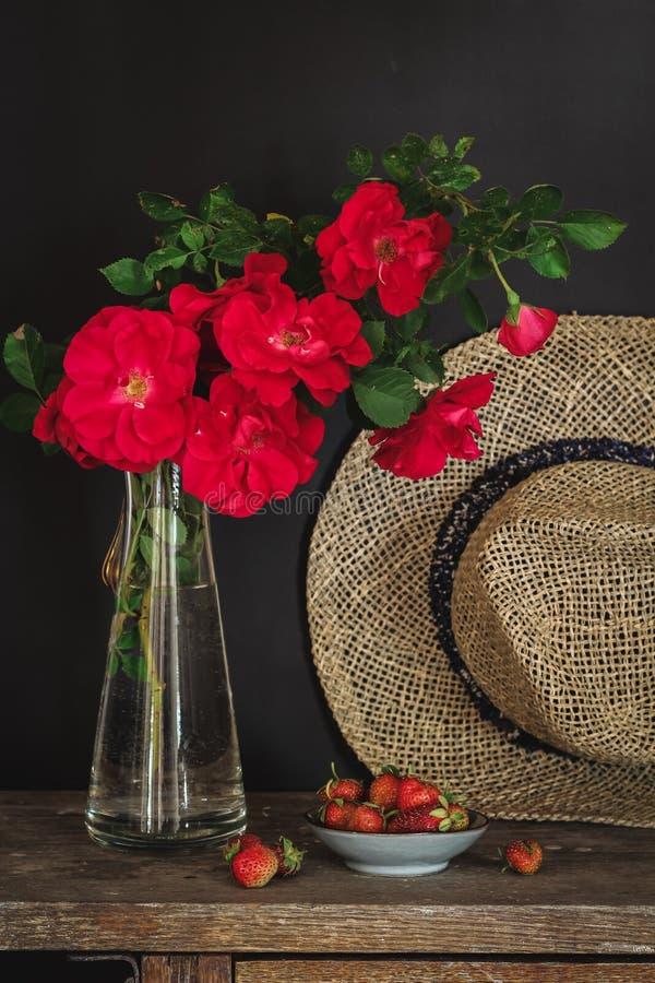 Rose rosse, fragole e un cappello su una vecchia tavola fotografie stock libere da diritti