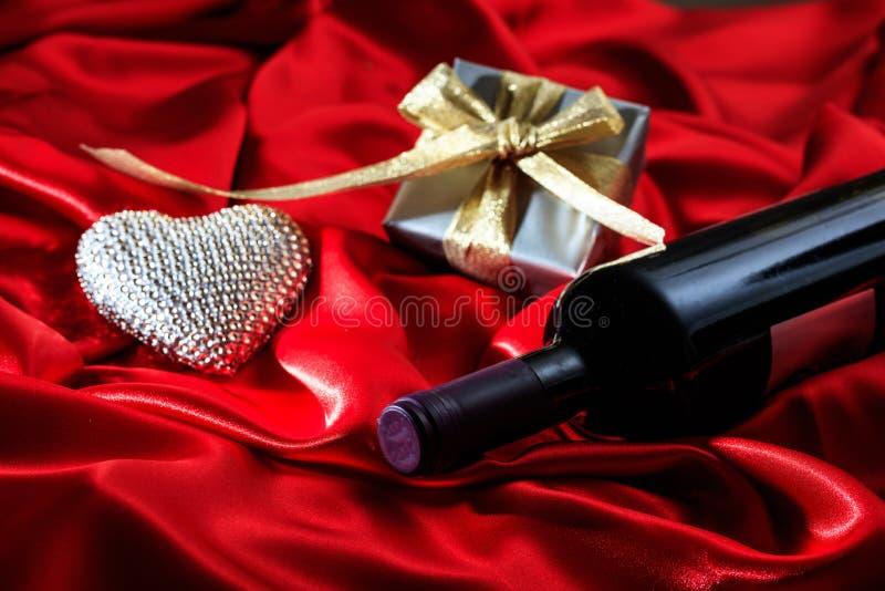 Rose rouge Bouteille de vin rouge, un cadeau et un coeur sur le satin rouge image libre de droits
