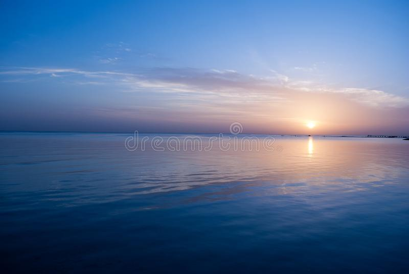 Rose sunrise on the ocean. Sun under the red sea in the morning. Sunset and reflex on water in the evening. Sunrise and blue sky stock photo