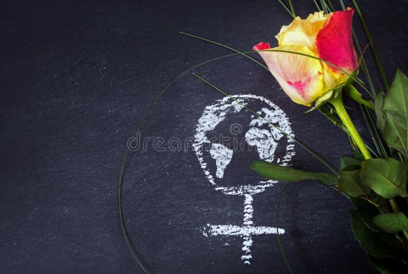 Rose und ein Kreide gezeichnetes weibliches Zeichen mit Erdkugel auf einem blackbo stockfotografie