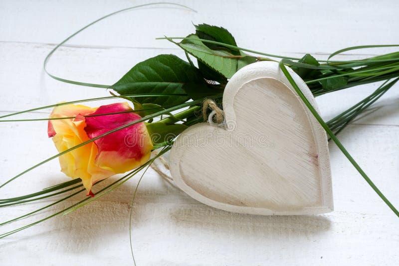 Rose und ein leeres hölzernes Herz auf Weiß malten Holz, Konzept FO lizenzfreie stockbilder