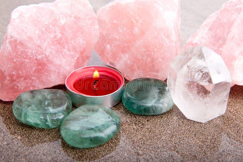 Rose und klarer Quarz, Flourite und rote Kerze stockfotos