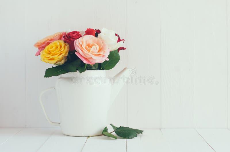 Rose variopinte in caffettiera bianca dello smalto fotografie stock libere da diritti