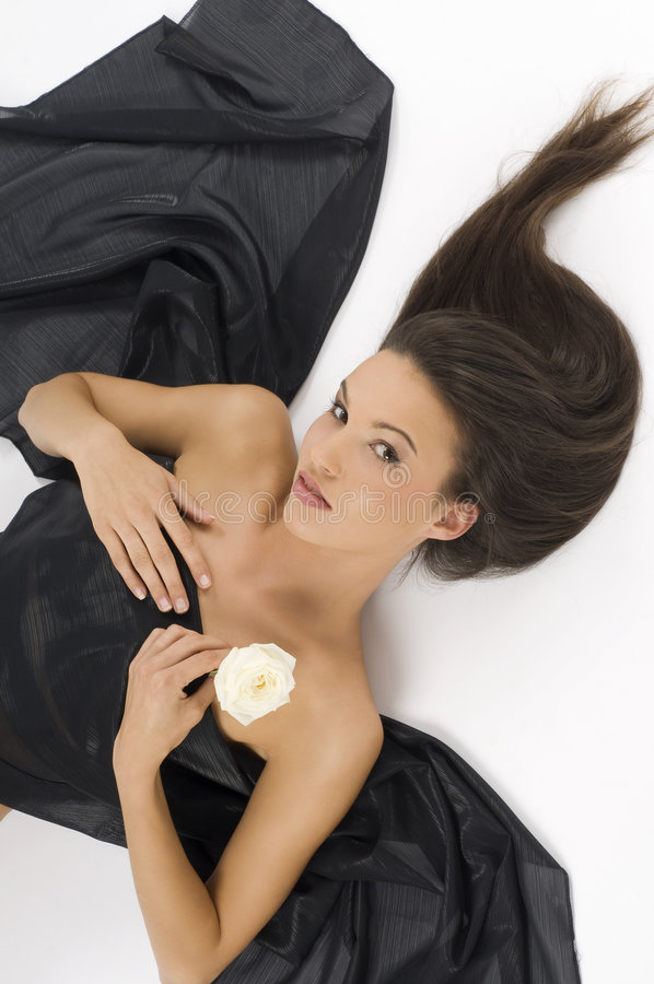 The rose and wave hair. Young and sweet brunette laying down with hair waved and a white rose royalty free stock photos