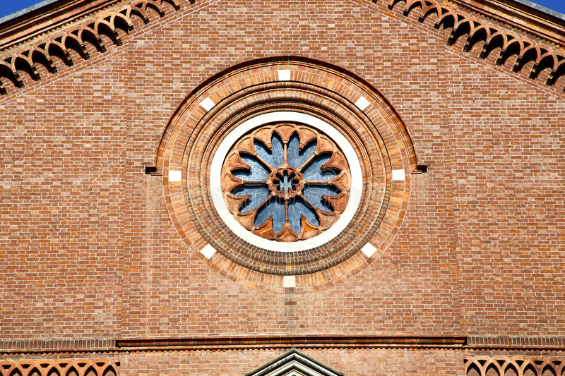 Rose window italy lombardy in the castellanza old br. Italy lombardy in the castellanza old church closed brick tower wall rose window tile royalty free stock photos