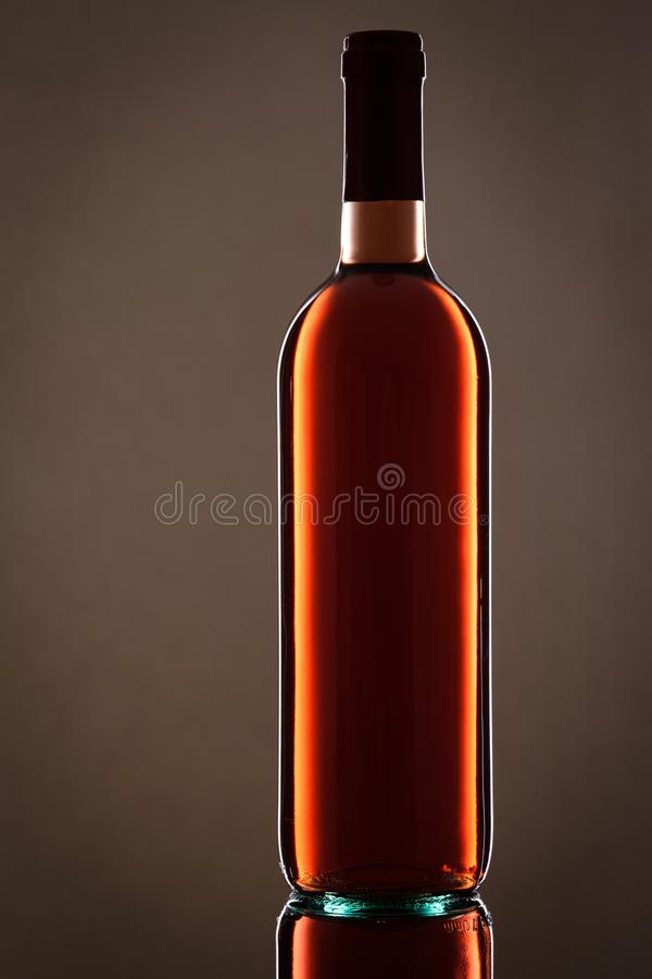 Rose wine bottle in vertical format. Rose wine bottle with light reflection in vertical format back lit stock photo