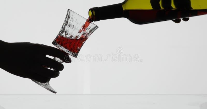 Rose Wine De rode wijn giet in wijnglas over witte achtergrond royalty-vrije stock afbeeldingen