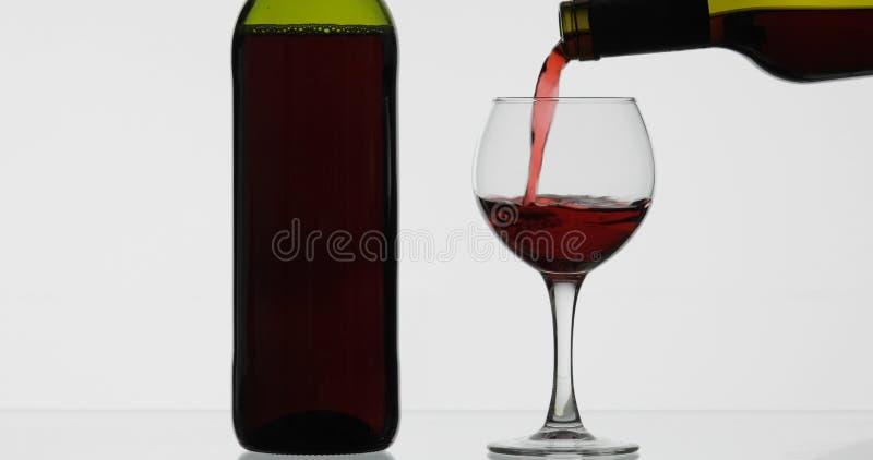 Rose Wine El vino tinto vierte la copa de vino sobre el fondo blanco imagen de archivo