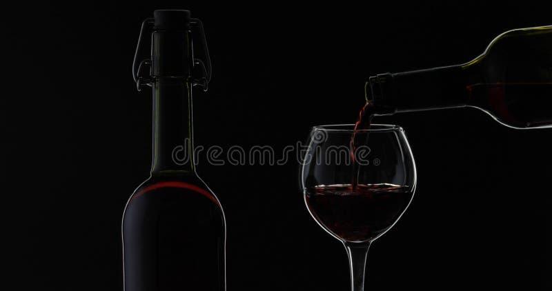 Rose Wine El vino tinto vierte la copa de vino sobre fondo negro Silueta fotos de archivo