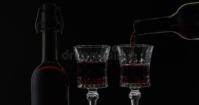 Rose Wine El vino tinto vierte la copa de vino sobre fondo negro Silueta fotografía de archivo libre de regalías