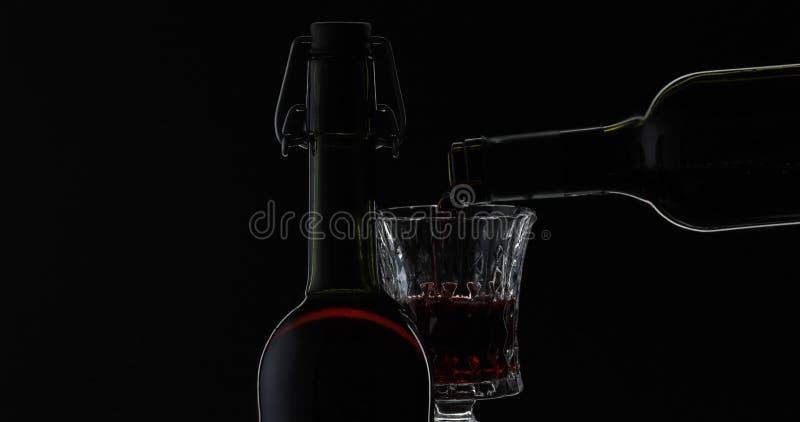 Rose Wine El vino tinto vierte la copa de vino sobre fondo negro Silueta imagen de archivo libre de regalías