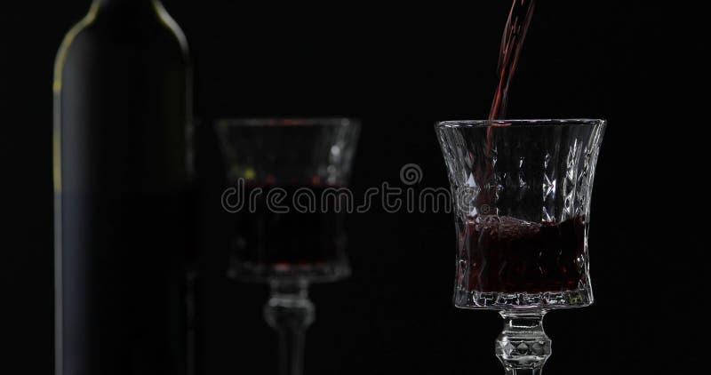 Rose Wine El vino tinto vierte la copa de vino sobre fondo negro Silueta imagenes de archivo