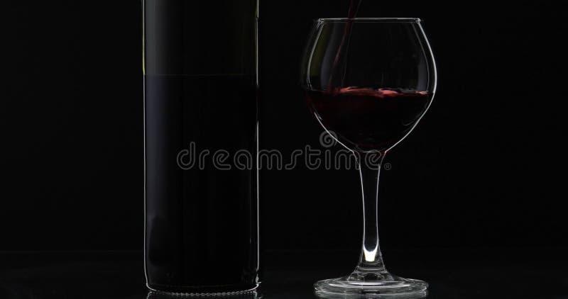 Rose Wine El vino tinto vierte la copa de vino sobre fondo negro Silueta imágenes de archivo libres de regalías