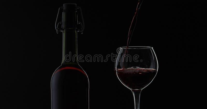 Rose Wine El vino tinto vierte la copa de vino sobre fondo negro Silueta fotografía de archivo