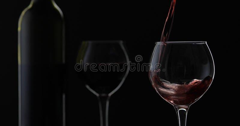 Rose Wine El vino tinto vierte la copa de vino sobre fondo negro Silueta foto de archivo libre de regalías