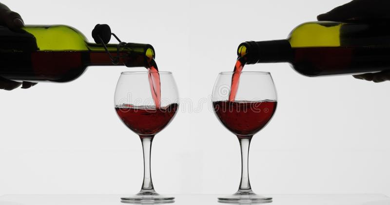 Rose wine. Red wine pour in two wine glasses over white background stock photo