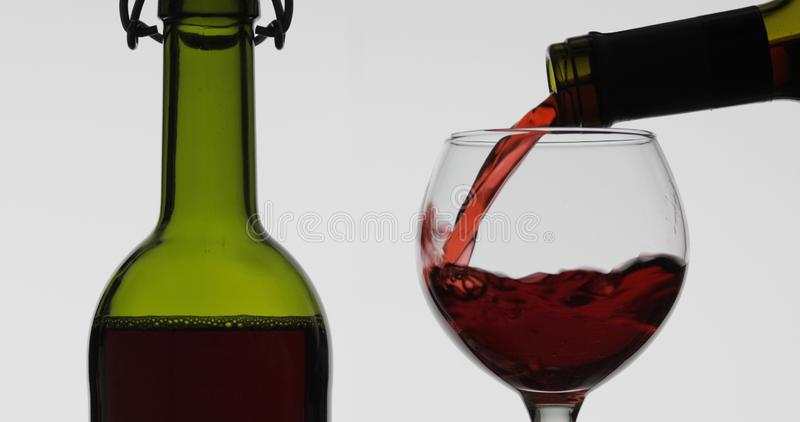 Rose wine. Red wine pour in wine glass over white background royalty free stock photos