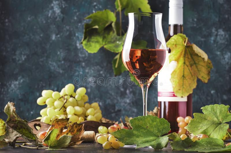 Rose wine at wine tasting concept. Gray background with grape and leaves. Pink wine in wineglass. Copy space stock photos