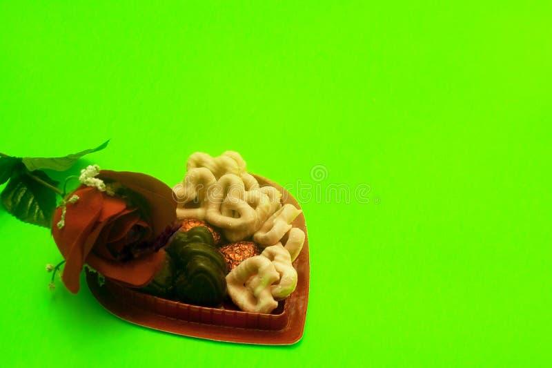 Rose y caja en forma de corazón con los pretzeles y los chocolates imagen de archivo
