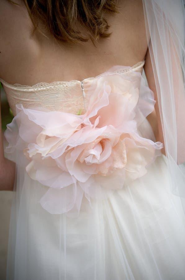 Roseapplique auf Hochzeitskleid einer Braut lizenzfreie stockfotografie