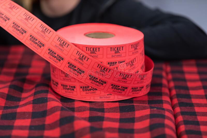 Staples double ticket roll on a table covered with black-n-red striped tablecloth stock photos