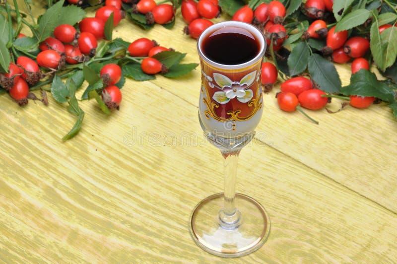 Rosehip owoc i alkoholiczka trunek w szkle obrazy royalty free