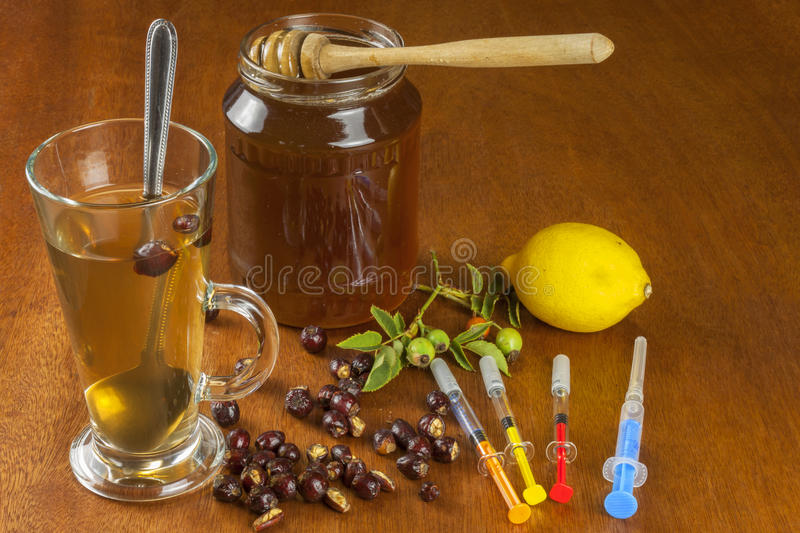 Rosehip tea and flu vaccination. Traditional medicine and modern treatment methods. Injection of influenza vaccine. Household treatment of flu and colds royalty free stock photo