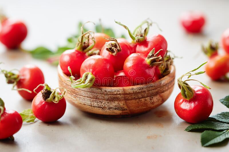Rosehips berries in small wooden bowl stock photos