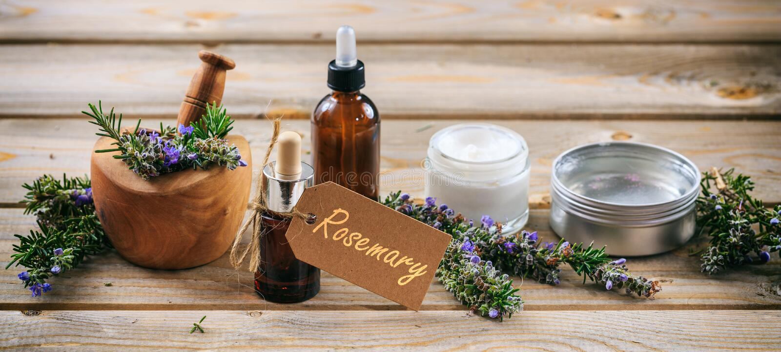 Rosemary aromatherapy. Essential oil and cosmetics, tag with text rosemary, banner. Wooden table background. Rosemary aromatherapy. Essential oil and cosmetics royalty free stock photo
