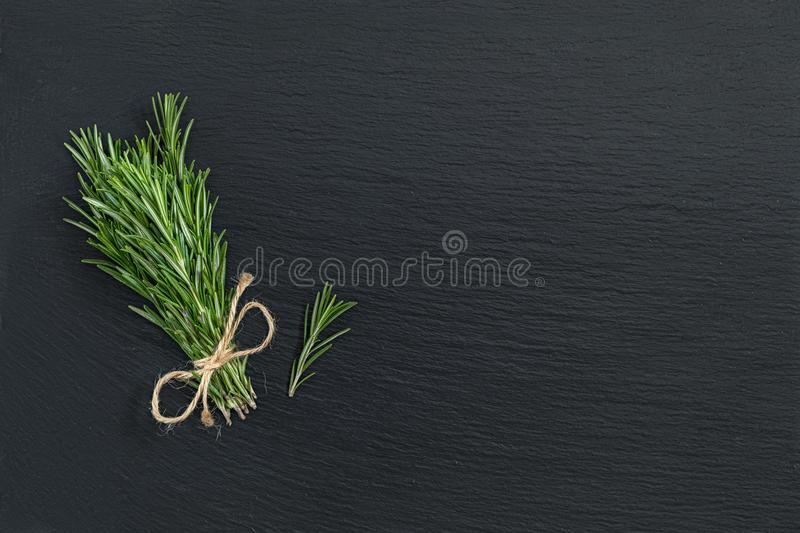Rosemary bunch of bouquets on black stone surface. Top view, cop. Y space stock photography