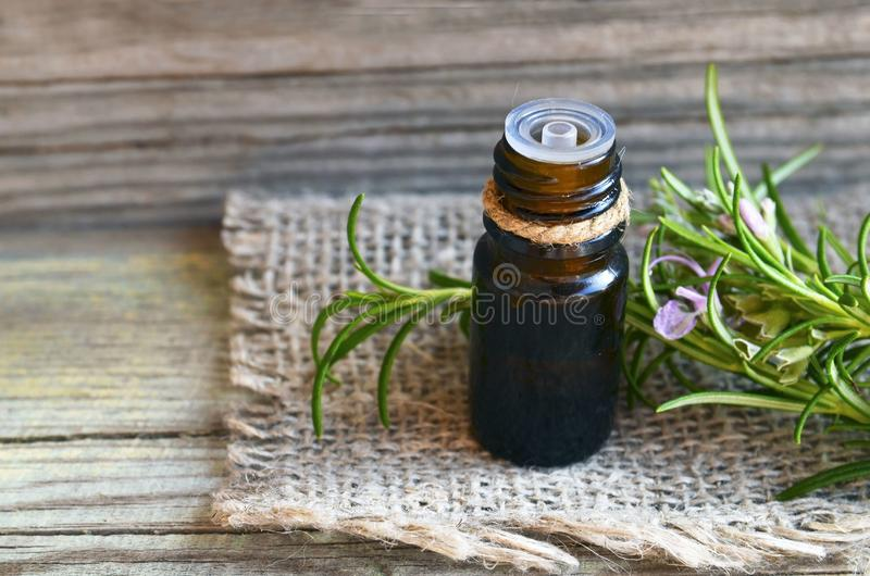 Rosemary essential oil in a glass dropper bottle with fresh green rosemary herb on old wooden table for spa,aromatherapy and body stock images