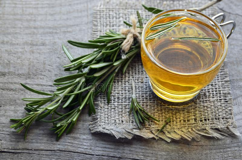 Rosemary herbal tea in a glass cup with fresh green rosemary herb on rustic wooden background. royalty free stock image