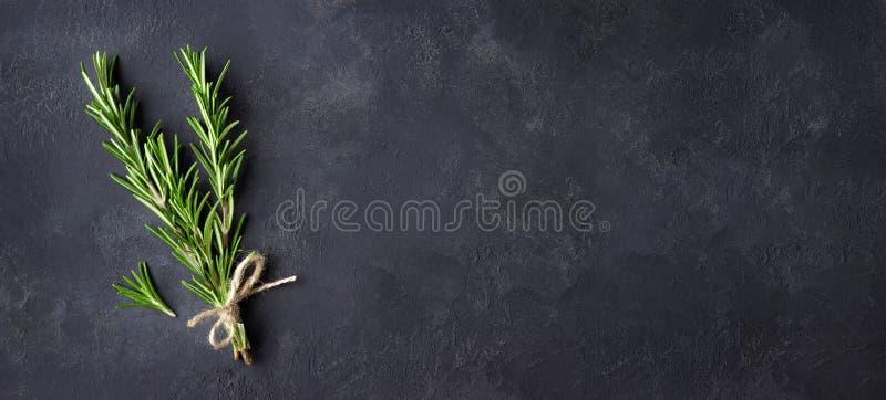 Rosemary kruiden op donkere steenachtergrond Exemplaarruimte voor menu of recept stock afbeelding