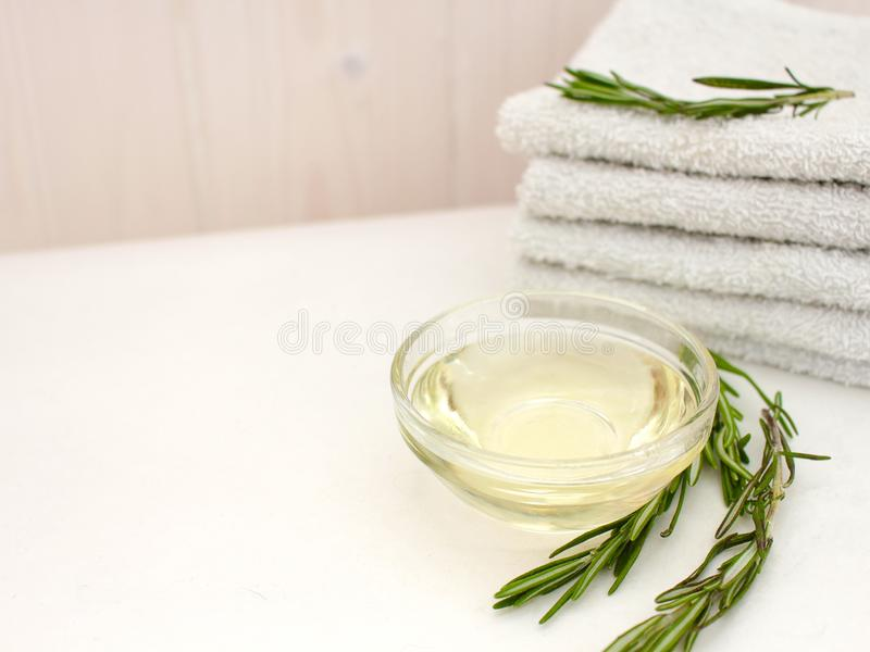 Rosemary oil and a branch of fresh rosemary with a stack of towels for face and body care on a wooden wall background. text entry stock image