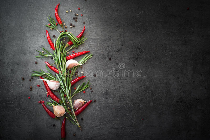 Rosemary, pepper and garlic on dark background. Seasoning background. Rosemary, pepper and garlic on dark background. Food ingredients with copy space royalty free stock image