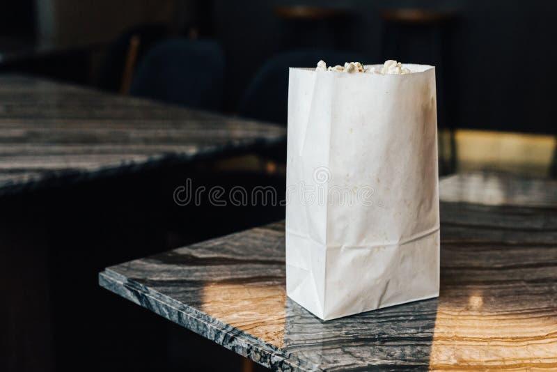Rosemary Popcorn i papperspåse marmorerar överst tabellen på vänstra sidan med kopieringsutrymme royaltyfri fotografi