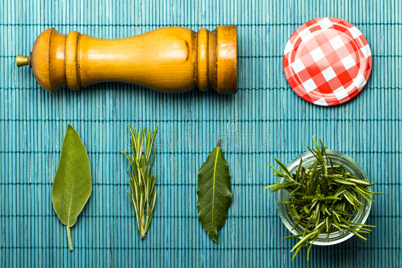 Rosemary , sage , and laurel leaves with a pepper mill. Flatlay of a rosemary , sage , and laurel leaves with a pepper mill royalty free stock image