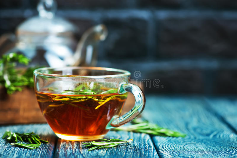 Rosemary tea. In cup and on a table stock images